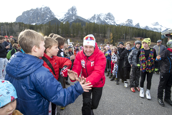 National Men's Cross Country Ski team coach Ivan Babikov high fives kids at the Frozen Thunder cross country ski track [P] Pam Doyle