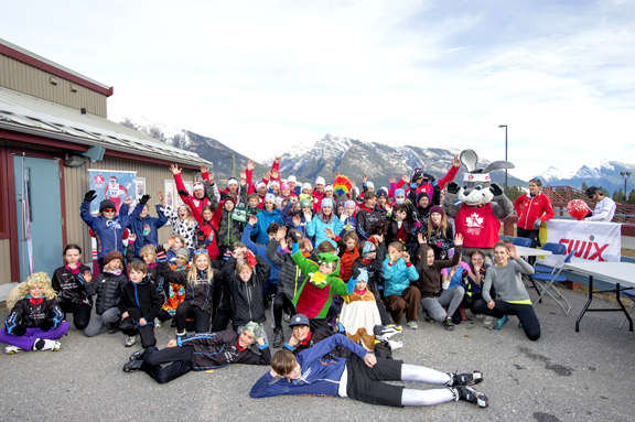 The National Cross Country Ski team and National Para Nordic Ski teams pose with children from the Canmore Nordic Ski Club and Foothills Nordic Ski Clubs after the kids relay [P] Pam Doyle