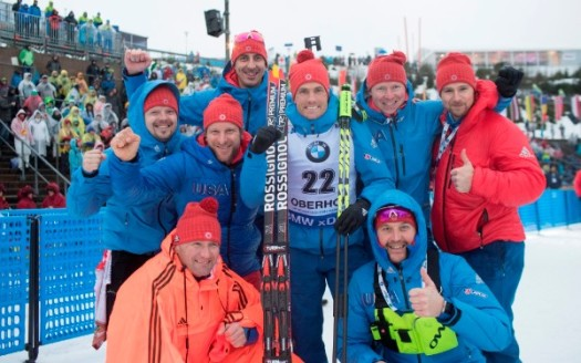 Tim Burke (center) celebrates his fourth-place finish in the men's 10-kilometer sprint with U.S. Biathlon coaches and staff [P] Nordic Focus